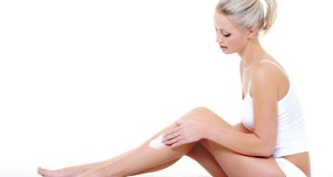 woman sitting on bed  applying moisturizer cream on her slim leg
