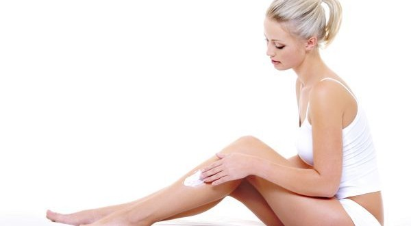 woman sitting on bed  applying moisturizer cream on her slim leg
