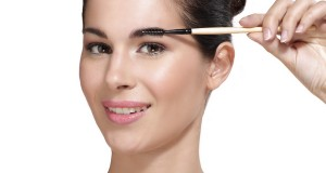 Beautiful young woman applying eyebrow brush